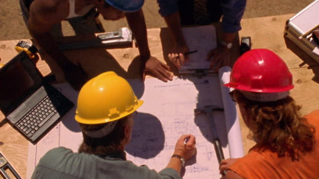 OVERHEAD zoom out four construction workers discussing blueprints on wooden table outdoors