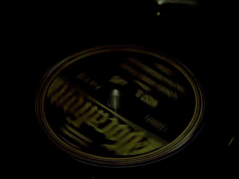 Zoom out from 78 rpm record playing on old-fashioned gramophone
