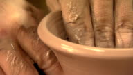 Zoom out from, a close up on clay being formed into a cup, to the artist