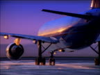 Zoom out from airplane taxiing along runway at sunrise