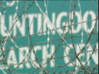 Zoom out from barbed wire to reveal Huntingdon Life Sciences sign