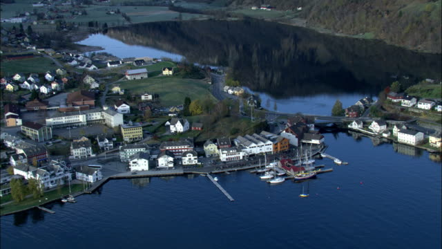 Zoom out from boat moored in harbour to reveal surrounding town on coast of Norway Available in HD.