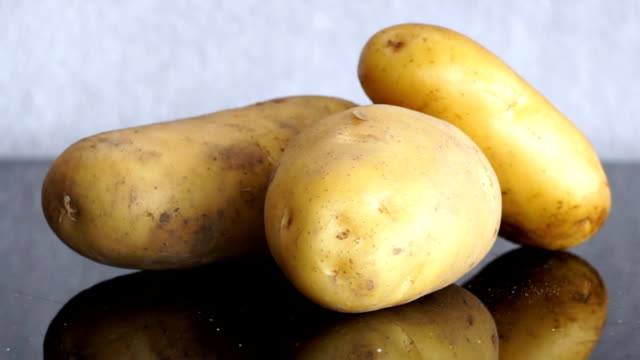 Zoom out from Bunch of Potatoes on a Table