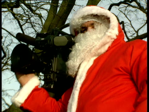 Zoom out from cameraman dressed in Santa suit standing on step ladder outside Sandringham church waiting for Royals Norfolk; 25 Dec 89