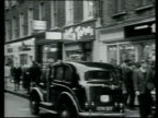 Zoom out from Carnaby Street sign to black taxi and mini parked in street and girls with sixties hair and clothes