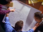 OVERHEAD zoom out from close up blueprint to businesspeople working at conference table
