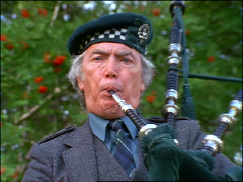 zoom out from close up of man in grey suit playing bagpipes outdoors / Birnam, Scotland