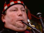 zoom out from close up of man playing bagpipes / Edinburgh, Scotland