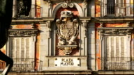 Zoom out from coat of arms on exterior of Casa de la Panaderia to view of pedestrians walking past statue of Felipe III at Plaza Mayor in fast motion / Madrid, Spain