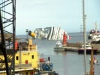 Zoom out from Costa Concordia capsized off the coast of Tuscany