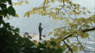 Zoom out from man fishing on wooden jetty at edge of Wolfgangsee to leaves on trees