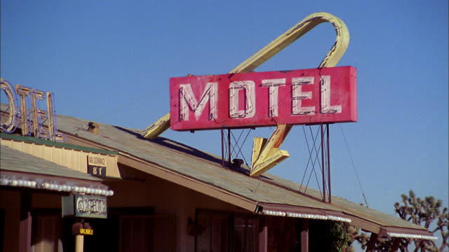 Zoom out from 'motel' sign on roof to entrance of motel w/trees and shrubs in background