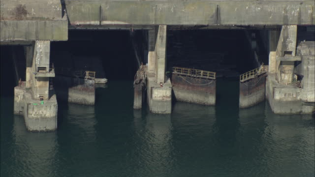 Zoom out from old U-boat submarine pens to an aerial shot of the Port of Lorient.