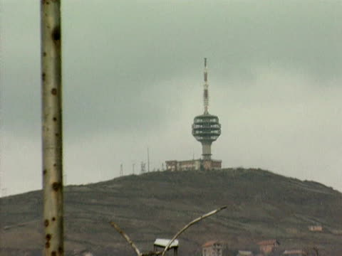 Zoom out from radio tower on hilltop to UN checkpoint Sarajevo 1994
