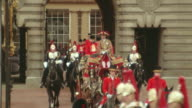 zoom out from royal carriage exiting gate of Buckingham Palace to royal guards on horseback in foreground / London
