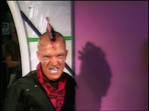 1981 zoom out from shadow to close up man with mohawk with flags attached + painted head turns + shows metal teeth