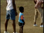 Zoom out from small child to men playing cricket Windward Islands
