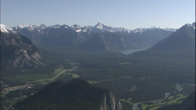 Zoom out from snowy mountain peaks to surrounding land and settlements, Canadian Rocky Mountains Park, Canada