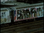 Zoom out from subway train covered in graffiti travelling along elevated railway