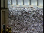 Zoom out from top of recycled paper heap pan left across vast paper recycling depot and staff