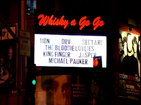 Zoom out from Whisky a Go Go sign to Sunset Strip with cars passing in front of club