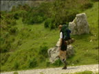 Zoom out from young man with backpack walking down a road winding through rocky hills large lake below Spain