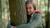 Zoom out girl hugging tree in woods and smiling at camera