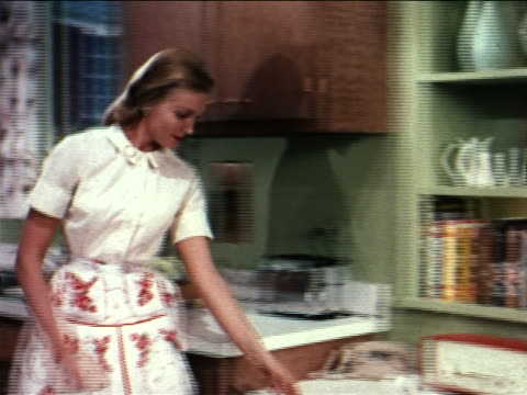1962 zoom out housewife putting cookbooks away, taking dish from oven + garnishing it / industrial