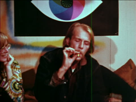1969 zoom out man lighting joint with match + passing it to woman with child who passes it on at party