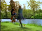 zoom out man playing bagpipes + woman dancing around sword + scabbard on grass near river / Scotland
