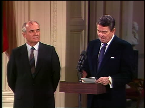 1987 zoom out Mikhail Gorbachev standing next to Ronald Reagan making speech at White House