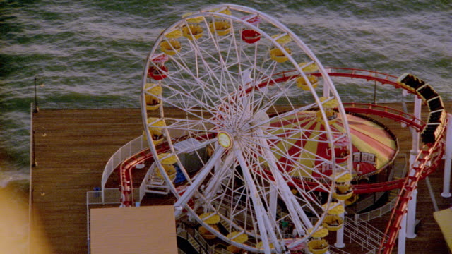 AERIAL zoom out over ferris wheel + amusement park rides on beach / Santa Monica Pier, California