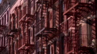 Zoom out pan fire escapes on brick building facades / NYC