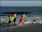 Zoom out pan right of a family running through the ocean surf. They are all wearing bathing suits and the children and mom are carrying innertubes.