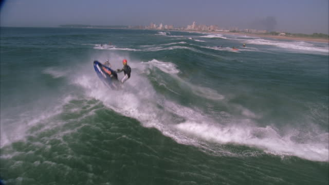 Zoom out, slow motion of a jetskier flying up into the air as he hits a wave