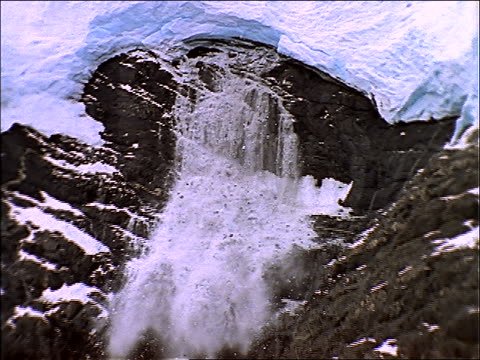 zoom out to wide shot of ice falling from glacier into water