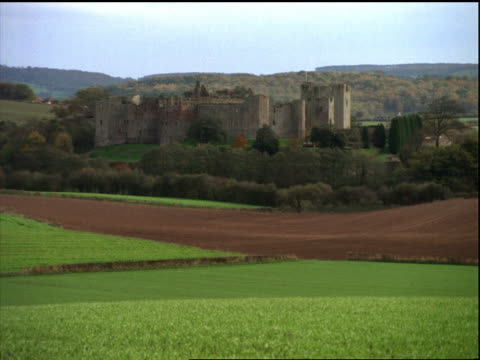 zoom out to wide shot of Raglan Castle ruins surrounded by countryside / England