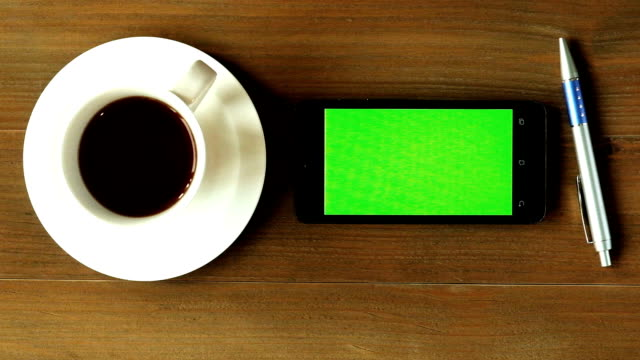 Zooma ut, Top Visa grön skärm smart telefon arbetar vid trä bord med kaffe och penna