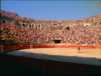 zoom out wide shot PAN matador raising arms to cheering crowd in bullfighting arena