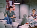 1952 zoom out woman pulling curtains out of washing machine talking to teenage girl sorting laundry