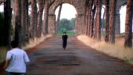 zoom out zoom in  priest walking away from aqueduct kicking ball to boys playing soccer on road / Italy