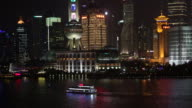 Zoomed panning view of a boat on the Huangpu River at night.