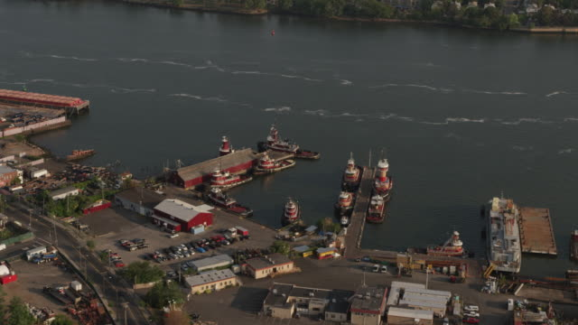 Zooming out shot of McCallister Towing tugboats docked in a harbor with the skyline of Manhattan in the background