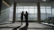 Zooming shot of silhouetted business people talking and shaking hands in lobby / Provo, Utah, United States,