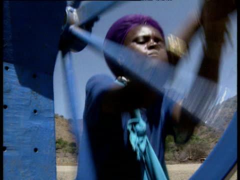 Zulu woman with purple headdress turns blue water pump wheel.