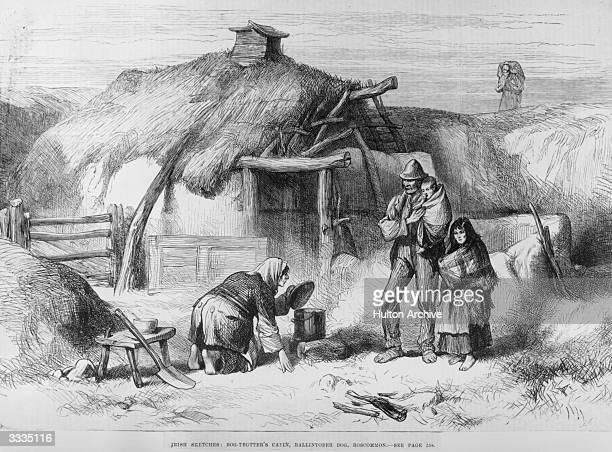 A barefoot family outside a ' bog trotter's' cabin in Roscommon Eire Food is cooking on a fire in the yard beside a roughly thatched shack Original...