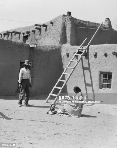 1930s NATIVE AMERICAN COUPLE BY ADOBE BUILDING WOMAN POLISHING POTTERY MAN LOOKING ON SANTA CLARA PUEBLO NEW MEXICO USA