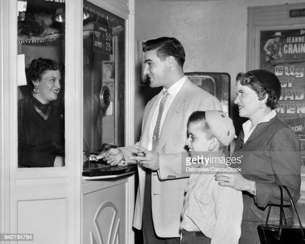 1950s FAMILY MOTHER FATHER BOY BUYING ADMISSION AT MOVIE THEATER TICKET BOX OFFICE