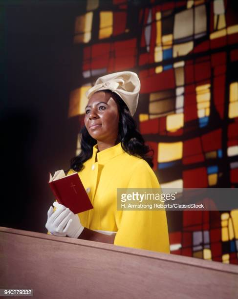 1960s 1970s AFRICAN AMERICAN WOMAN CHURCH PEW SILLY WHITE HAT GLOVES YELLOW CAPE HOLDING RED PRAYER BOOK