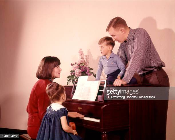 1960s FAMILY SINGING AROUND PIANO MOTHER PLAYING MUSIC SEATED ON BENCH WITH DAUGHTER FATHER AND SON ALSO SINGING